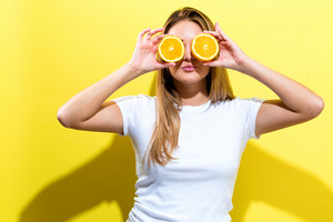 Happy young woman holding oranges halves on a yellow background