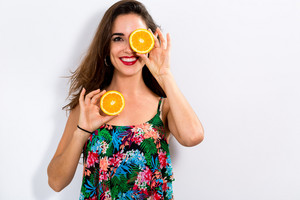 Happy young woman holding oranges on a white background
