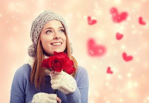 Happy young woman holding red roses with hearts