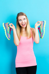 Happy young woman holding shoes on a blue background