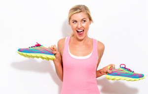 Happy young woman holding shoes on a white background