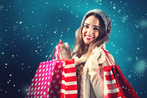 Happy young woman holding shopping bags in snowy night