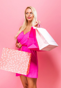 Happy young woman holding shopping bags on a pink background