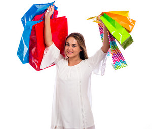 Happy young woman holding shopping bags on a white background