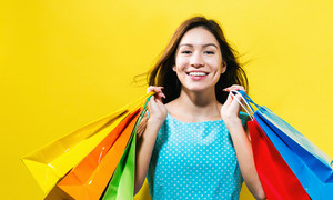 Happy young woman holding shopping bags on a yellow background