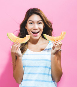 Happy young woman holding slices of cantaloupe on a pink background