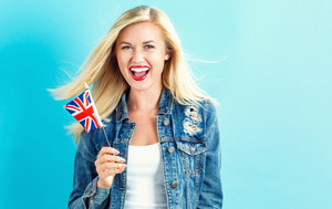 Happy young woman holding Union Jack flag on a blue background