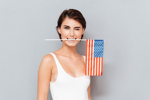 Happy young woman holding USA flag in teeth and winking over gray background