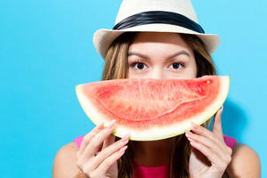 Happy young woman holding watermelon on a blue background