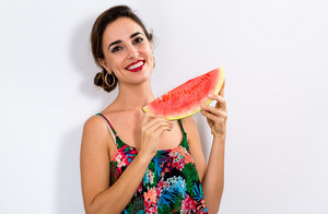 Happy young woman holding watermelon on a white background