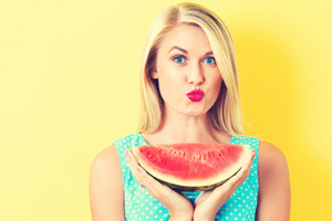Happy young woman holding watermelon on a yellow background