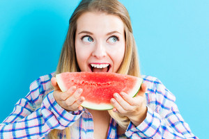 Happy young woman holding watermelon on blue background