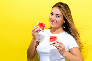 Happy young woman holding watermelons on a yellow background