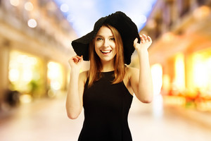 Happy young woman in a black hat at the mall