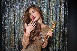 Happy young woman in evening dress laughing and holding award over sparkling background