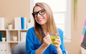 Happy young woman in glasses in her home office with a cup of green tea