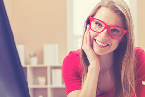 Happy young woman in glasses smiling in her home office