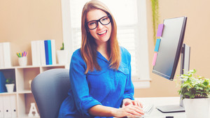 Happy young woman in glasses using a her computer in her home office