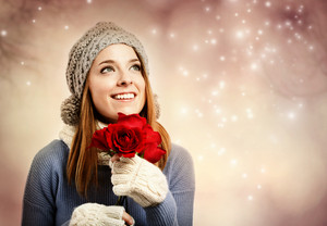 Happy young woman in winter clothes holding red roses
