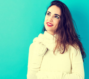 Happy young woman in winter clothes on a blue background
