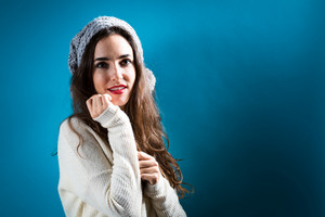 Happy young woman in winter clothes on a dark blue background