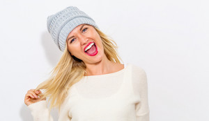 Happy young woman in winter clothes on a white background