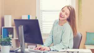 Happy young woman laughing in her home office