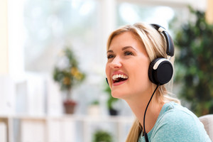 Happy young woman listening to music on headphones at home
