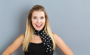 Happy young woman on a gray background