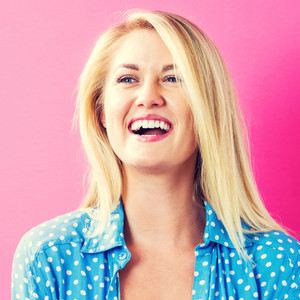 Happy young woman on a pink background