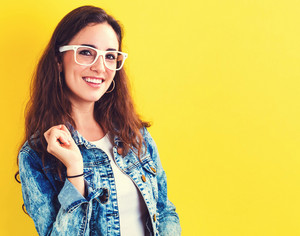 Happy young woman on a yellow background