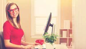 Happy young woman on her computer in her home office
