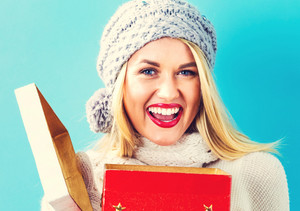 Happy young woman opening a Christmas present box