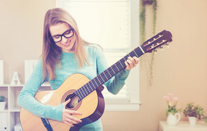 Happy young woman playing guitar in her house