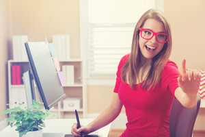 Happy young woman pointing to somethine while working with a pen stylus tablet in her home office
