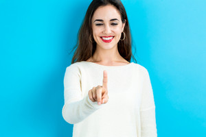 Happy young woman pointing to something on a blue background