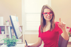 Happy young woman pointing to something while working with a pen stylus tablet in her home office