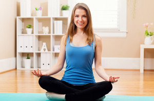 Happy young woman practicing meditation at home