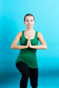 Happy young woman practicing meditation on a blue background