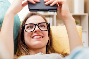 Happy young woman reading an e-book on her couch at home