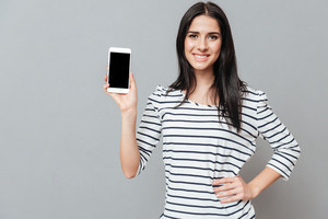 Happy young woman showing phone display to the camera over grey background. Look at camera.