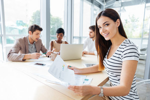 Happy young woman sitting and creating presentation with her business team in office