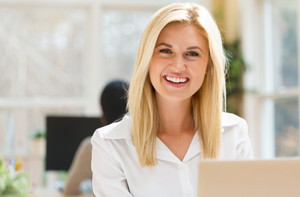 Happy young woman sitting at her desk in front of the computer
