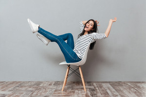 Happy young woman sitting on stool over grey background. Look at camera.