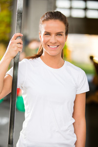 Happy young woman smiling at fitness gym center