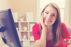Happy young woman smiling in her home office