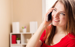 Happy young woman speaking on the phone in her home office