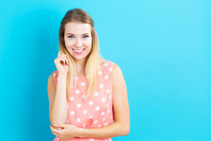 Happy young woman standing in front of a pink background