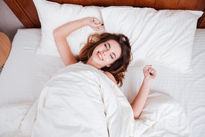 Happy young woman stretching hands while lying on bed at home