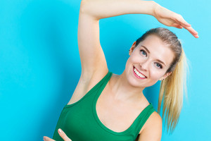 Happy young woman stretching on a blue background